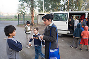 The NGO 'ARCI' taking Roma Gypsy children to school early morning. Roma Gypsies victims of racism and discrimination, often forcibly evicted or moved from one camp to another, marginalized, living on the periphery of urban centres. The Roma Gypsies originated from India where they left over a thousand years before. Tribes moved across Euroasia eventually arriving in Europe in the 14th century. They have survived 500 years of slavery and persecution. They moved from place to place, often nomadic in search of work. Now many live in container camps, some are unemployed, others work the markets, or import export. Rome, Italy.