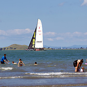 NZL 41 America's Cup Yacht  passes families playing in the water at Cheltenham Beach, Auckland,  New Zealand, 7th November 2010. Photo Tim Clayton