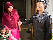 17 JUNE 2015 - RANGAE, NARATHIWAT, THAILAND: Thai Army Ranger 2nd Lt MONTHA SOMPIASERT, right, talks to a Thai Muslim woman in her home. Her son was injured three years ago by a bomb set by insurgents in an IED attack. The Rangers bring the family food and perform wellness checks as a part of the Rangers' outreach program. There are 5 platoons of women Rangers serving in Thailand's restive Deep South. They generally perform security missions at large public events and do public outreach missions, like home wellness checks and delivering food and medicine into rural communities. The medics frequently work in civilian clothes because the Rangers found people are more relaxed around them when they're in civilian clothes. About 6,000 people have been killed in sectarian violence in Thailand's three southern provinces of Narathiwat, Pattani and Yala since a Muslim insurgency started in 2004. Attacks usually spike during religious holidays. Insurgents are fighting for more autonomy from the central government in Bangkok.     PHOTO BY JACK KURTZ