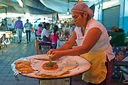 Mexican woman making traditional food in a street food market. Oaxaca is known throughout Mexico and internationally for it's great food. Seen as a centre for Mexican cuisine, among other regional specialities the dish the area is best known for is called Mole.