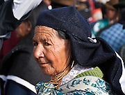 A traditional woman with gold necklaces attends Otavalo Market in Ecuador, Imbabura Province, South America. The culturally vibrant town of Otavalo attracts many tourists to a valley of the Imbabura Province of Ecuador, surrounded by the peaks of Imbabura 4,610m, Cotacachi 4,995m, and Mojanda volcanoes. The indigenous Otavaleños are famous for weaving textiles, usually made of wool, which are sold at the famous Saturday market and smaller markets during the rest of the week. The Plaza del Ponchos and many shops tantalize buyers with a wide array of handicrafts. Nearby villages and towns are also famous for particular crafts: Cotacachi, the center of Ecuador's leather industry, is known for its polished calf skins; and San Antonio specializes in wood carving of statues, picture frames and furniture. Otavaliña women traditionally wear distinctive white embroidered blouses, with flared lace sleeves, and black or dark over skirts, with cream or white under skirts. Long hair is tied back with a 3cm band of woven multi colored material, often matching the band which is wound several times around their waists. They usually have many strings of gold beads around their necks, and matching tightly wound long strings of coral beads around each wrist. Men wear white trousers, and dark blue ponchos. Otavalo is also known for its Inca-influenced traditional music (sometimes known as Andean New Age) and musicians who travel around the world.