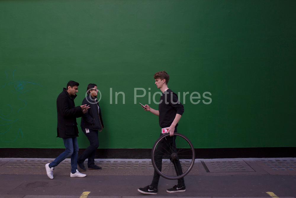 Street Scene of people passing by a green painted wall on in Soho, London, England, United Kingdom. The simplicity of the scene helps highlight the figures of ordinary people going about their daily lives. One man carrying a bicycle wheel.