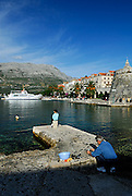 Korcula old town, with man cleaning fish and child sitting on bollard of stone jetty. Korcula old town, island of Korcula, Croatia