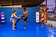 """17 DECEMBER 2104 - BANGKOK, THAILAND: The Kanisorn boxing gym is a small gym along the Wong Wian Yai - Samut Sakhon train tracks. Young people from the nearby communities come to the gym to learn Thai boxing. Muay Thai (Muai Thai) is a Thai fighting sport that uses stand-up striking along with various clinching techniques. It is sometimes known as """"the art of eight limbs"""" because it is characterized by the combined use of fists, elbows, knees, shins, being associated with a good physical preparation that makes a full-contact fighter very efficient. Muay Thai became widespread internationally in the twentieth century, when practitioners defeated notable practitioners of other martial arts. A professional league is governed by the World Muay Thai Council. Muay Thai is frequently seen as a way out of poverty for young Thais and Muay Thai camps and schools are frequently crowded. Muay Thai professionals and champions are often celebrities in Thailand.     PHOTO BY JACK KURTZ"""