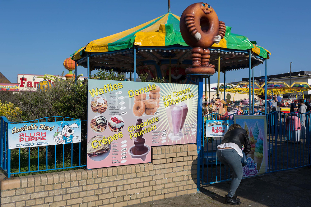 A menu sign advertising poor nutrition of sugary snacks including donuts and waffles near a childrens fairground, on 29th April 2017, at Hastings, East Sussex, England.