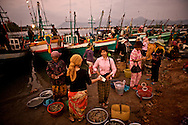 Women complete a transaction at the fish market in Kampot.  Shrimp boats have arrived in the pre-dawn hours and the shrimp are immediately sold for the day's market in town.