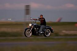 A man rides his chopper down the freeway near the airport