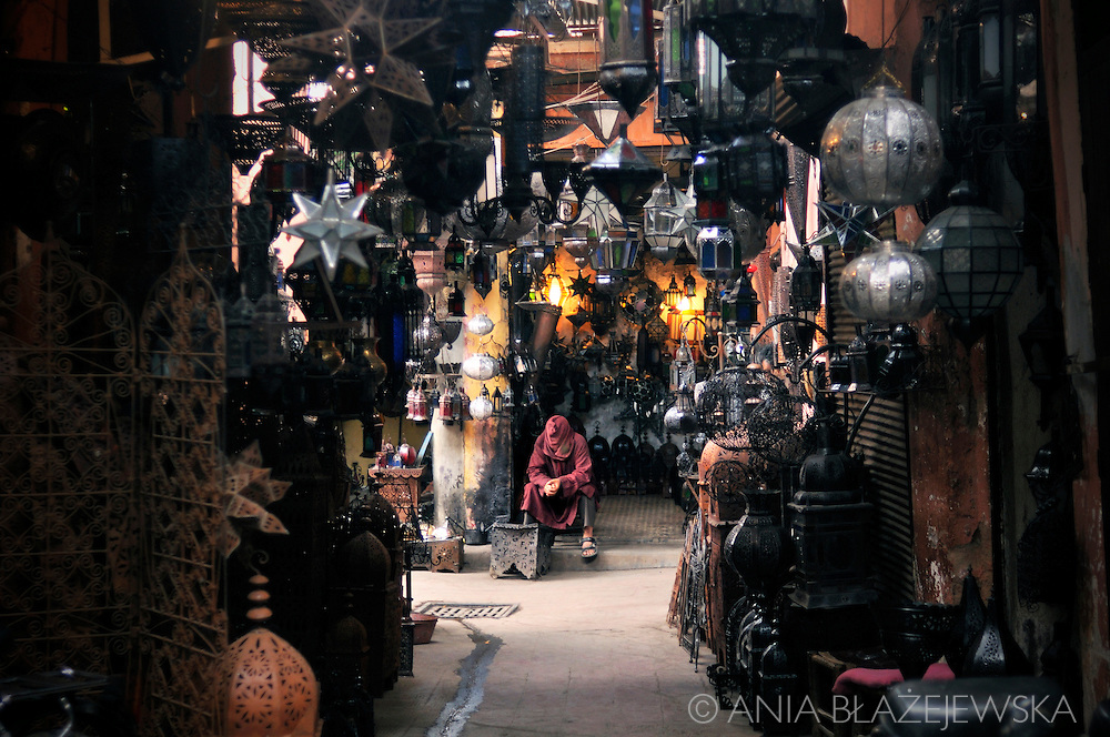 Morocco. Souks in Marrakesh. Lamp shop and a man wearing a hood.
