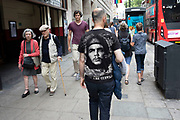 Rear view of a man wearing a Che Guevara t-shirt in London, United Kingdom. Ernesto Che Guevara was an Argentine Marxist revolutionary, physician, author, activist, guerrilla leader, diplomat and major figure of the Cuban Revolution, his stylized visage has become a ubiquitous countercultural symbol of rebellion and global insignia in popular culture.