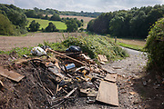 A heap of dumped, fly-tipped waste on a countryside footpath, on 27th August 2017, near Cobham, Kent, England.