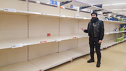 © Licensed to London News Pictures. 12/03/2020. London, UK. A shopper points at empty shelves as Sainsbury's store in London runs out of toilet rolls amid an increased number of cases of Coronavirus (COVID-19) in the UK. 590 cases have been tested positive and ten patients have died from the virus in the UK. Photo credit: Dinendra Haria/LNP