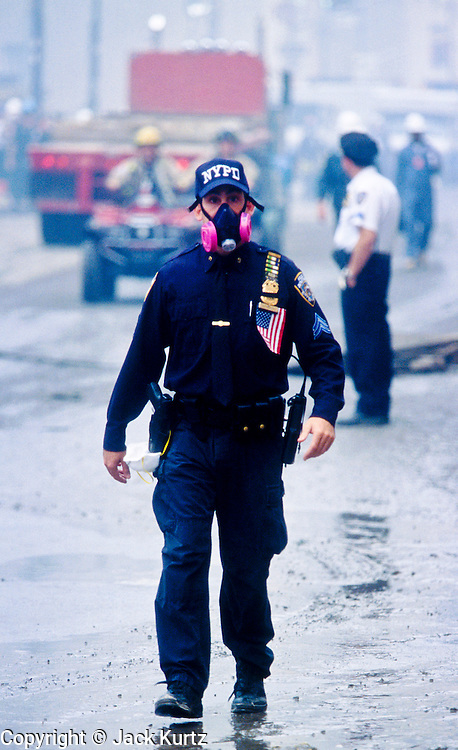 """NEW YORK, NY: A New York police officer wearing a breathing filter walks through the dust and smoke at """"Ground Zero"""" of the World Trade Center complex after the WTC terrorist attack, Sept. 22, 2001. Almost 3,000 people were killed when terrorists crashed hijacked passenger jets into the twin towers. PHOTO BY JACK KURTZ"""