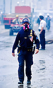 "NEW YORK, NY: A New York police officer wearing a breathing filter walks through the dust and smoke at ""Ground Zero"" of the World Trade Center complex after the WTC terrorist attack, Sept. 22, 2001. Almost 3,000 people were killed when terrorists crashed hijacked passenger jets into the twin towers. PHOTO BY JACK KURTZ"