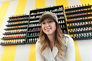Polished Nail Bar owner Leslie Rupe poses for a photograph in front of a large selection of nail-polish colors on Tuesday at her shop.