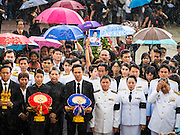 19 OCTOBER 2014 - BANG BUA THONG, NONTHABURI, THAILAND: The Wiriyachai family stands in the rain in front of a mourner holding up a photo of Apiwan Wiriyachai during his cremation at Wat Bang Phai in Bang Bua Thong, a Bangkok suburb, Sunday. Apiwan was a prominent Red Shirt leader. He was member of the Pheu Thai Party of former Prime Minister Yingluck Shinawatra, and a member of the Thai parliament and served as Yingluck's Deputy Prime Minister. The military government that deposed the elected government in May, 2014, charged Apiwan with Lese Majeste for allegedly insulting the Thai Monarchy. Rather than face the charges, Apiwan fled Thailand to the Philippines. He died of a lung infection in the Philippines on Oct. 6. The military government gave his family permission to bring him back to Thailand for the funeral. His cremation was the largest Red Shirt gathering since the coup.     PHOTO BY JACK KURTZ