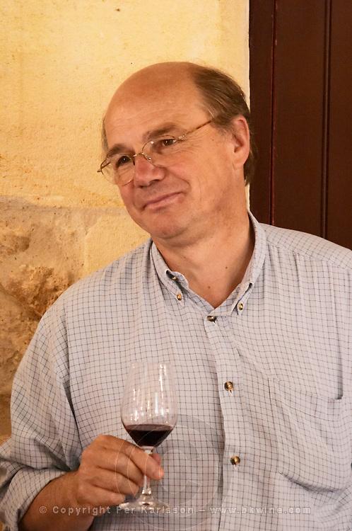 Jean-Francois Quenin, owner and wine maker, in the tasting room holding a glass of his wine  Chateau de Pressac St Etienne de Lisse  Saint Emilion  Bordeaux Gironde Aquitaine France