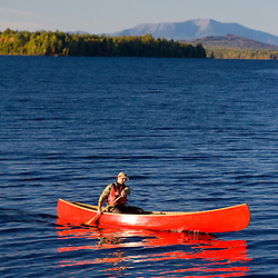 A man paddles his canoe on Seboeis Lake near Millinocket, Maine.  Mount Katahdin is in the distance. (MR)