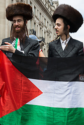 Ultra-Orthodox anti-Zionist Haredi Jews from Neturei Karta UK stand holding a Palestinian flag during a United Against The Tories national demonstration organised by the People's Assembly Against Austerity in protest against the policies of Prime Minister Boris Johnson's Conservative government on 26th June 2021 in London, United Kingdom. The demonstration contained blocs from organisations and groups including Palestine Solidarity Campaign, Stand Up To Racism, Stop The War Coalition, Extinction Rebellion, Kill The Bill and Black Lives Matter as well as from trade unions Unite and the CWU.