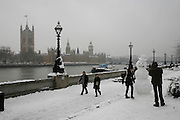 Weather, climate change. London, Britain and Europe, is gripped by a big freeze. Winter conditions which are likened to Siberia swept across Europe, bringing traffic and transport to a halt, closing schools and stopping millions of people going to work. Whilst most buses and tubes were not working, some commuters and tourists got to central London to enjoy the freak snow.///Commuters and tourists walk past a huge snowman wearing a hat stands on the opposite bank of the Thames river to the Westminster and the Houses of Parliament