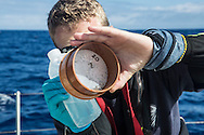 North Atlantic Ocean, October 2014.<br /> Marine biologist Adam Porter rising a sample recovered from a trawl, days away from land, on board the Sea Dragon. © Chiara Marina Grioni