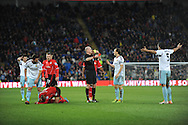 West Ham's James Tomkins (No.5) can't believe he's receiving a 2nd yellow and a red card as he is sent off by ref Lee Mason during the Barclays Premier league, Cardiff city v West Ham Utd match at the Cardiff city Stadium in Cardiff, South Wales on Saturday 11th Jan 2014.<br /> pic by Jeff Thomas, Andrew Orchard sports photography.