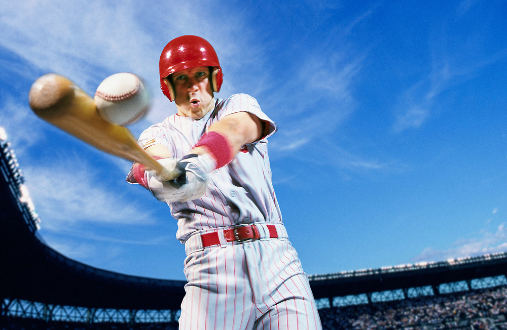 A professional baseball player swinging and hitting a baseball.