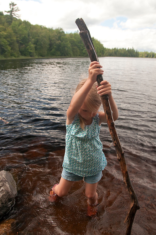 A young girl plays near the water at Craig Lake State Park near Michigamme Michigan.