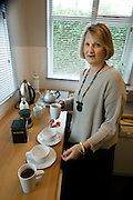Fenella Hodson, prepares tea for guests at home in Godalming, UK. (Material World Family from Great Britain UK) MODEL RELEASED.