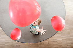 Little boy playing with red balloons in kindergarten, elevated view