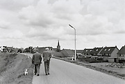 Two men walking down a road Holland