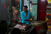 Members of a small family traditional Chinese Opera troupe prepare for a performance in a hidden shrine in Chinatown, Bangkok.