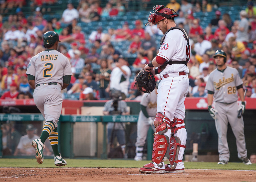 The Angels' Jett Bandy looks at the ground as the Athletics' Kris Davis scores after his solo home run in the second inning at Angel Stadium on Tuesday.<br /> <br /> ///ADDITIONAL INFO:   <br /> <br /> angels.0803.kjs  ---  Photo by KEVIN SULLIVAN / Orange County Register  -- 8/2/16<br /> <br /> The Los Angeles Angels take on the Oakland Athletics at Angel Stadium.