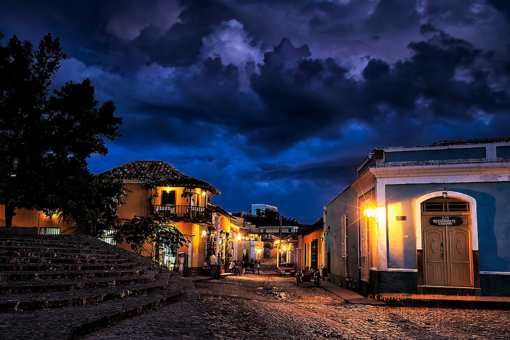 Storm Over Trinidad: Looking out from an empty Plaza Mayor at sunset, restaurants and cafes are devoid of tourists as storm clouds amass overhead, Trinidad Cuba.