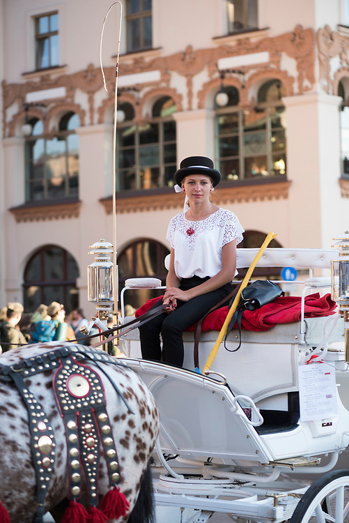 Krakow, Poland - August 27, 2016: A Polish woman sits in her horse-drawn carriage in Krakow's Rynek Glowny square, waiting for a fare. The carriages are popular with tourists.