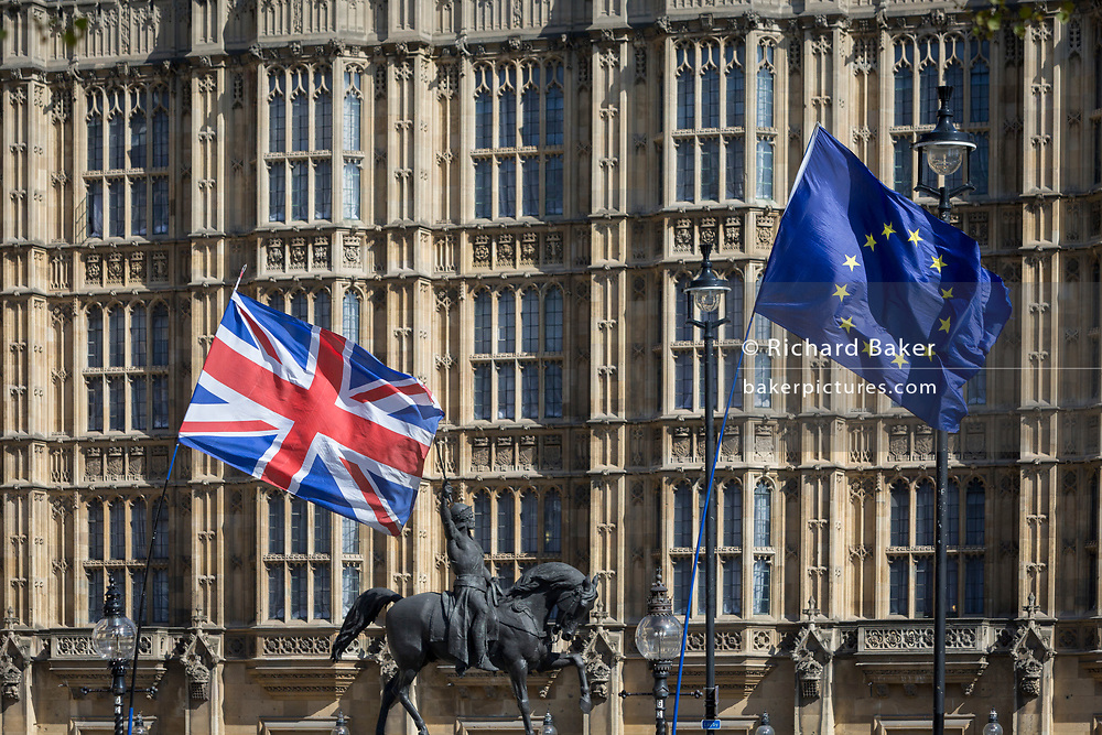 On the day that Prime Minister Theresa May returns to Brussels to negotiate an expected Brexit delay, the EU flag and Union jack fly as pro-EU remainers protest opposite parliament in Westminster, in London, England.