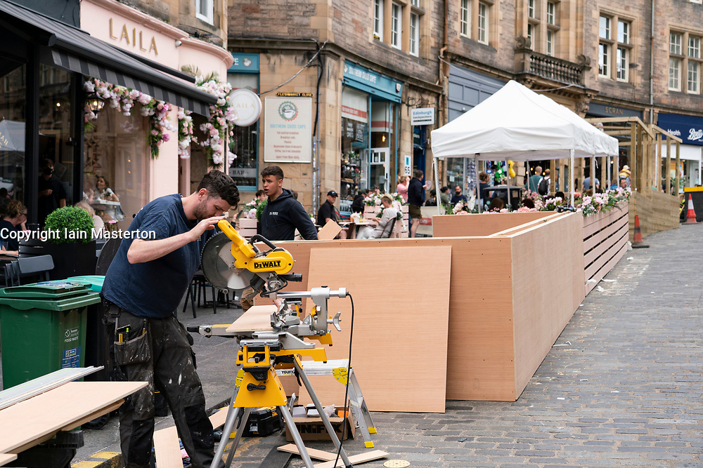 Edinburgh, Scotland, UK. 10 June 2021. With few overseas tourists in Edinburgh because of Coronavirus travel restrictions, many tourist shops on the Royal Mile are closed or suffering financial difficulties. Many have put signs in windows accusing the SNP Scottish Government of not doing enough to help save jobs. Pic; Cafes are building outdoor terraces  on the street to attract more customers here on Cockburn Street in Old Town . Iain Masterton/Alamy Live News