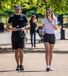 © Licensed to London News Pictures. 20/05/2020. London, UK. A couple enjoy an ice cream in the sunshine in Hyde Park as weather experts predict the warmest day of the Year with a high of 27c. Last week the Government eased the law on lockdown to let people spend more time outside to enjoy sunbathing and picnicking. Photo credit: Alex Lentati/LNP