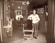 view of a barbershop with two men posing by the barber chairs 1900 USA