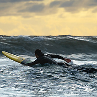 surfer paddling out at sunrise on north yorkshire coast