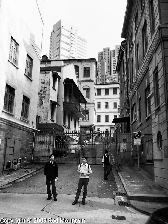Young men waiting near a side street in Hong Kong. Photo: © Rod Mountain<br /> <br /> http://www.rodmountain.com<br /> @rod_mountain<br /> https://twitter.com/rod_mountain<br /> <br /> http://bit.ly/HK-SideStreet