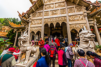 Buddhists touching a guardian statue for good luck at the Temple of Southern Buddhism, Yuantong Temple, Kunming, Yunnan Province, China.