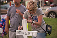 Penny Toledo writes a message on a cross for a fallen officer in Baton Rouge.