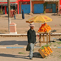North Africa, Africa, Morocco, Marrakesh. Man with hat stands near oranges for sale on the street.
