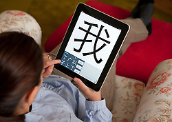 Female student learning mandarin Chinese using education application on iPad tablet computer