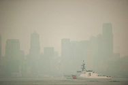 2018 AUGUST 20 - A US Coast Guard cutter sails in Elliott Bay with downtown buildings as a backdrop as smoke fills the skies of Seattle, WA, USA. Seen from near Don Armeni Boat Ramp in West Seattle. By Richard Walker