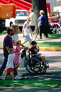 Family pushing brother in wheelchair with oxygen ages 36 and 5 thru 7.  St Paul  Minnesota USA