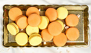 Stack of orange and yellow macaroon biscuits isolated on white.