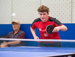 © Licensed to London News Pictures. 18/07/2019; Bristol, UK. National Table Tennis Day in the UK. LOUIS PRICE age 15, Junior England International, plays with Maria Tsapsinos, National Singles Champion and Bronze medallist in the 2018 Commonwealth Games in the Ping Pong Parlour in the Galleries Shopping Centre. Photo credit: Simon Chapman/LNP.
