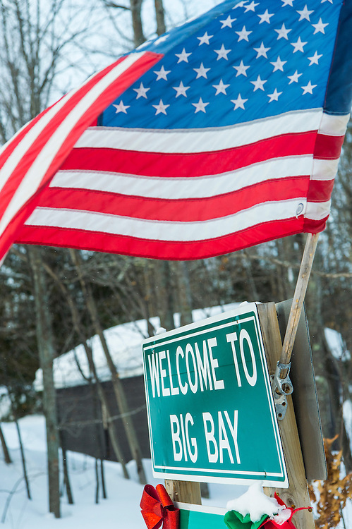 Signs and an American Flag welcome visitors to Big Bay, Michigan.