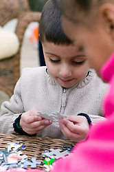 Little boy putting pieces of a jigsaw together,